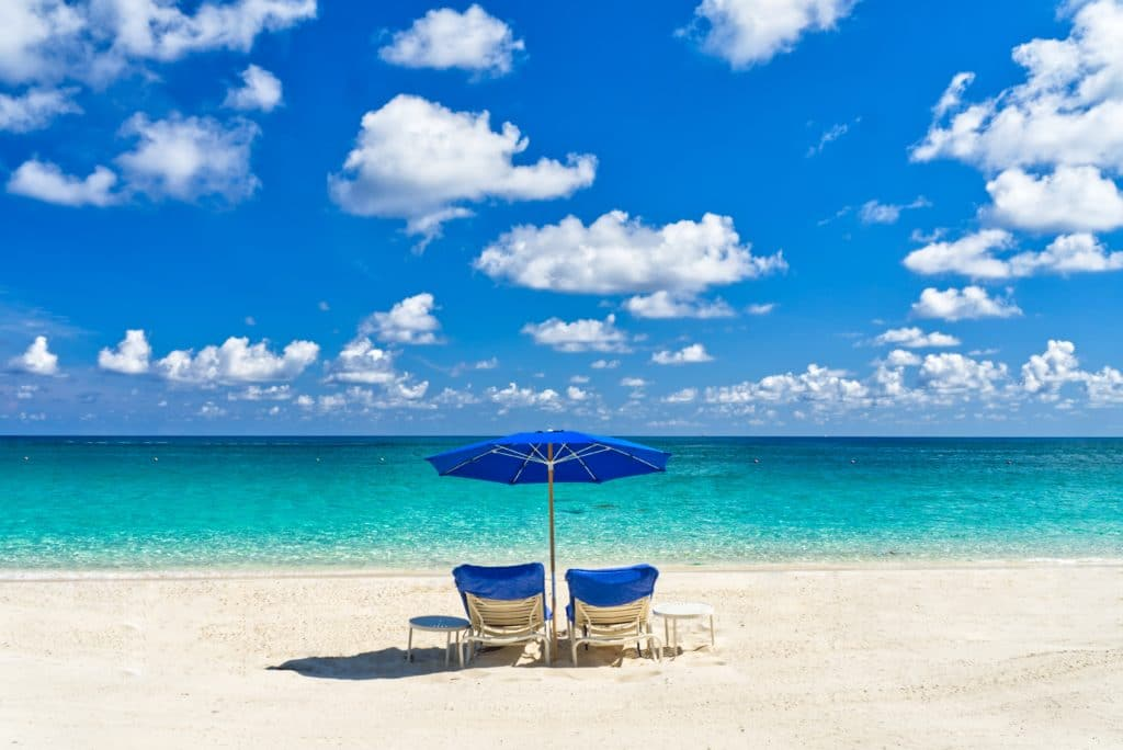 Beach chairs and a blue umbrella on a pristine Bahamas beach.